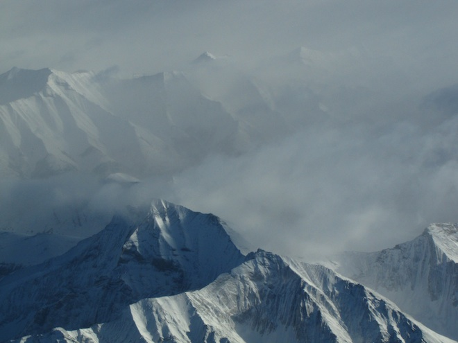 """Вершины гор """"курятся"""" словно вершины вулканов: но это снег, сдуваемый ветром с гор. Вся та облачность на заднем плане есть не что иное, как масса ледяных кристаллов поднятых в небо сильным ветром. Я так думаю, что ветер обдувал вершины со скоростью не менее 130-140 км/ч."""
